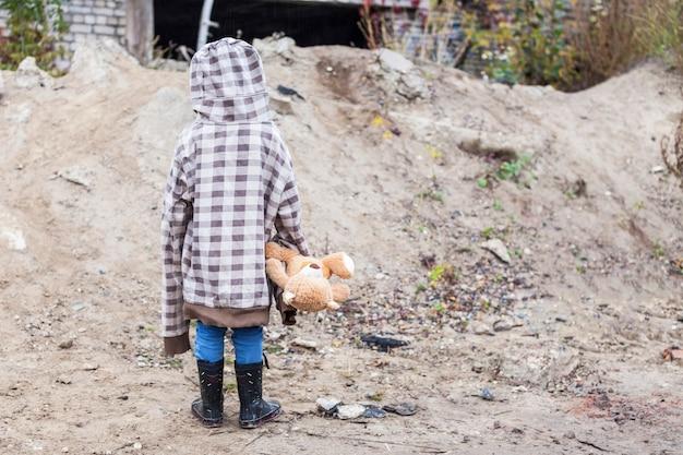 Een kleine jongen in grotere kleding staat met een beer in zijn handen op verlaten plaatsen Premium Foto