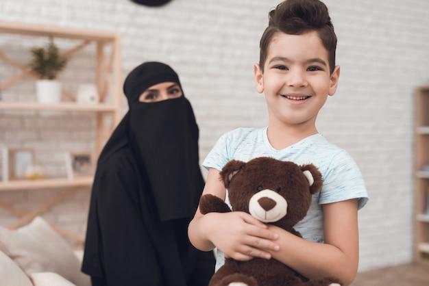 Een kleine jongen uit een arabische familie houdt een speelgoedbeer vast. Premium Foto
