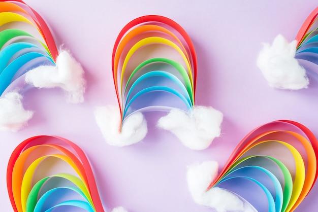 Een kleine regenboog van gekleurd papier met sneeuwwolken, creativiteit met hun handen op een lichte achtergrond. diy Premium Foto