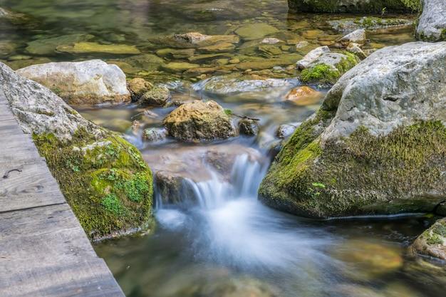 Een kleine schilderachtige rivier stroomt tussen de stenen in het bos. Premium Foto