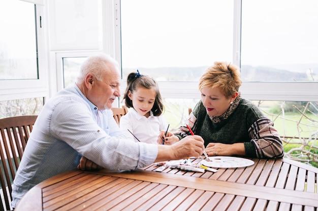Een kleine vrouw met haar grootouders schildert enkele tekeningen op het terras van haar huis met aquarelverf Premium Foto
