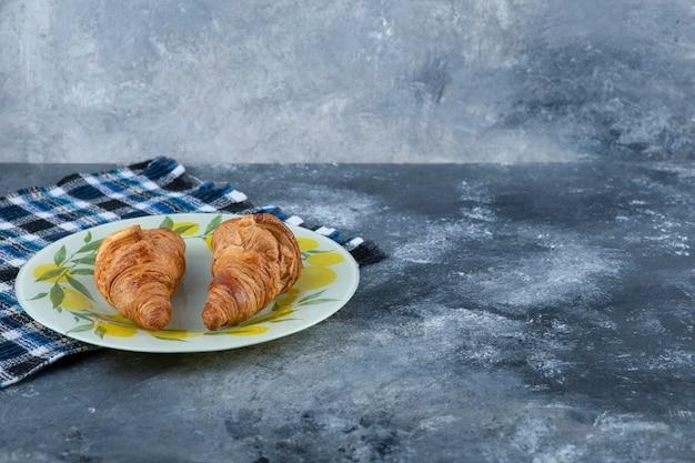 Een kleurrijk bord met verse croissants op een marmeren tafel. Gratis Foto