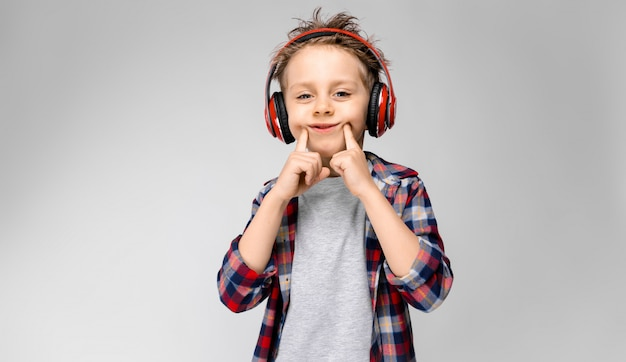 Een knappe jongen in een geruit hemd, grijs shirt en spijkerbroek staat. een jongen in een rode koptelefoon. de jongen strekt zijn vingers uit met een glimlach. Premium Foto