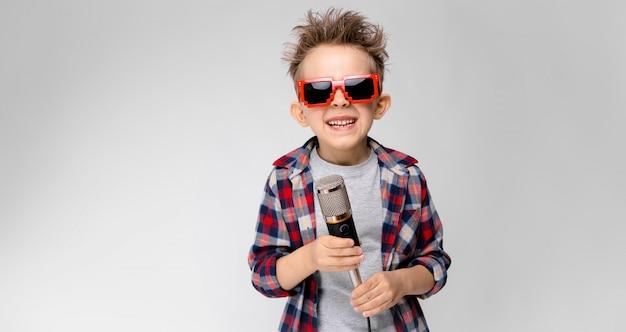 Een knappe jongen in een geruite hemd, grijs shirt en spijkerbroek staat Premium Foto