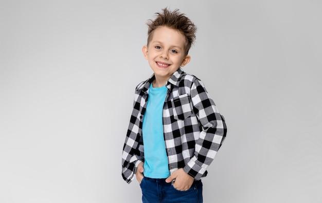 Een knappe jongen in een plaid shirt, blauw shirt en spijkerbroek staat op een grijze achtergrond. de jongen glimlacht en steekt zijn handen in de zakken van zijn spijkerbroek Premium Foto