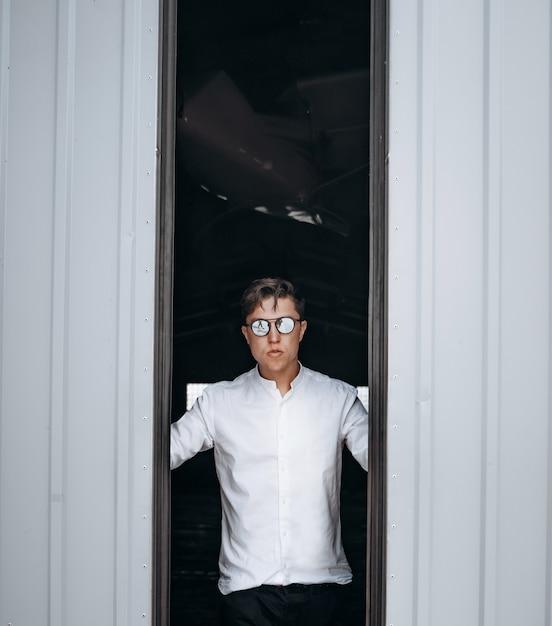 Een knappe man in zonnebril opent de deur naar de hangar. Gratis Foto