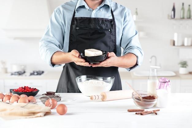 Een kok met eieren op een rustieke keuken tegen de achtergrond van mannenhanden Gratis Foto