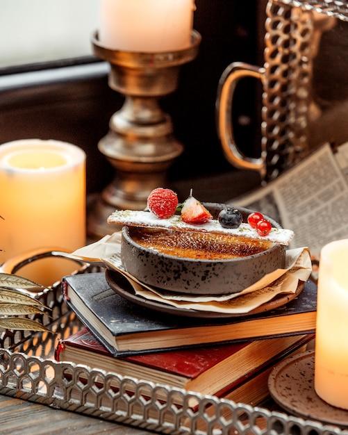 Een kom van frans dessert gegarneerd met bessen geplaatst op het boek Gratis Foto