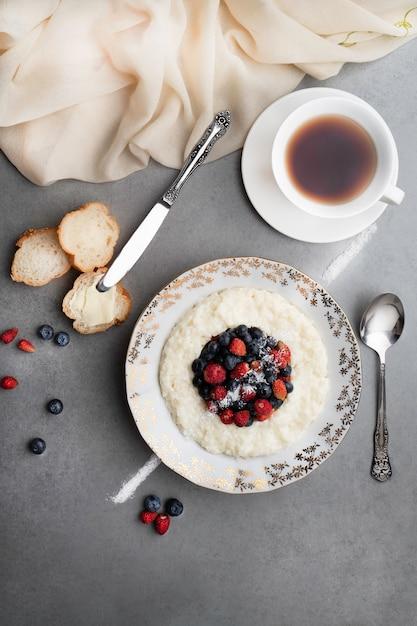 Een kop thee en rijstebrij met bessen op een grijze steenachtergrond. Premium Foto