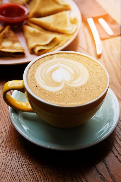 Een kopje cappuccino op een houten tafel in het café. koffiepauze. Premium Foto