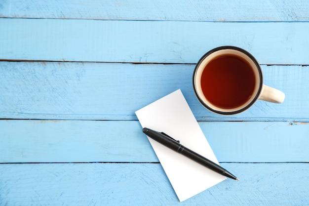 Een kopje drank en een papieren notitieblok met een zwarte pen op een blauw hout Premium Foto