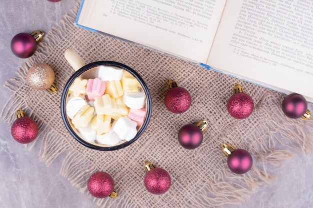 Een kopje drank met marshmallows en rode kerstballen rond Gratis Foto
