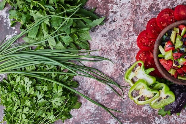 Een kopje groentesalade geserveerd met kruiden apart. Gratis Foto