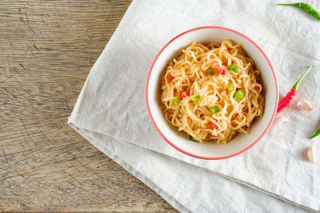 Een kopje instant noedels geplaatst op een servet met chili als ingrediënten, bovenaanzicht noodle en copyspace Premium Foto