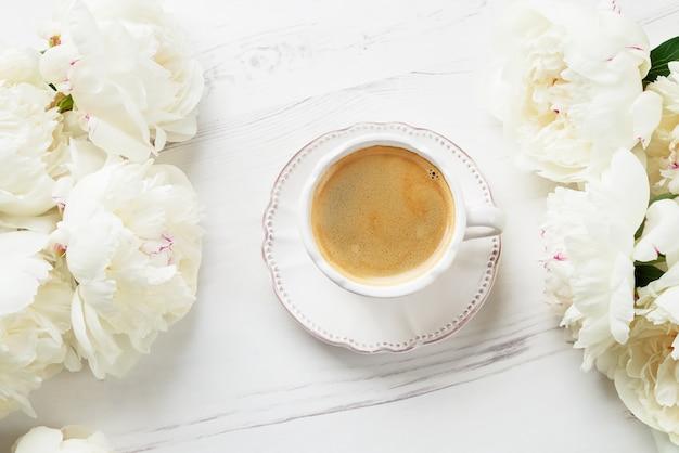 Een kopje koffie en witte pioenrozen op witte houten achtergrond. Premium Foto