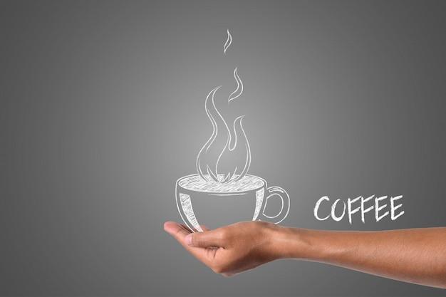 Een kopje koffie geschreven in wit krijt in zijn hand, tekenen concept. Gratis Foto