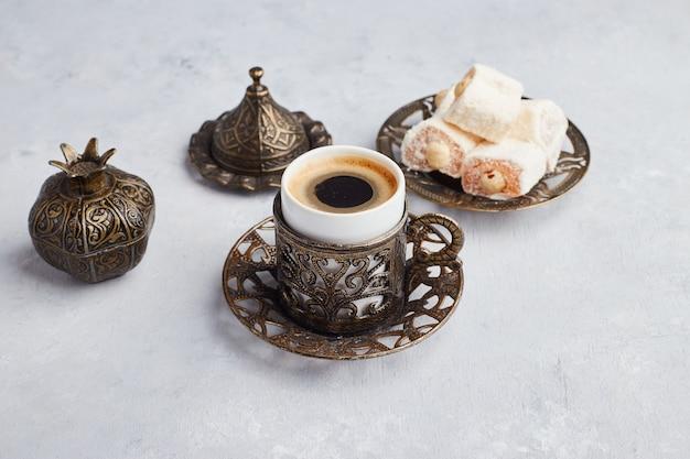 Een kopje koffie geserveerd met turkse lokum op witte tafel. Gratis Foto