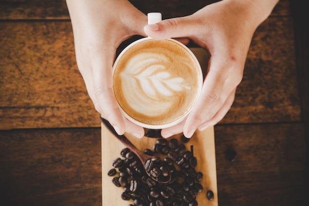 Een kopje koffie in de hand van vrouwen op houtstructuur. Gratis Foto