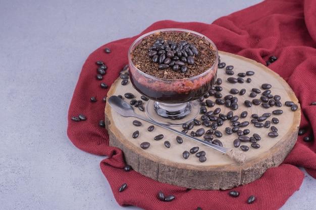 Een kopje koffie met chocoladebonen op een houten bord. Gratis Foto