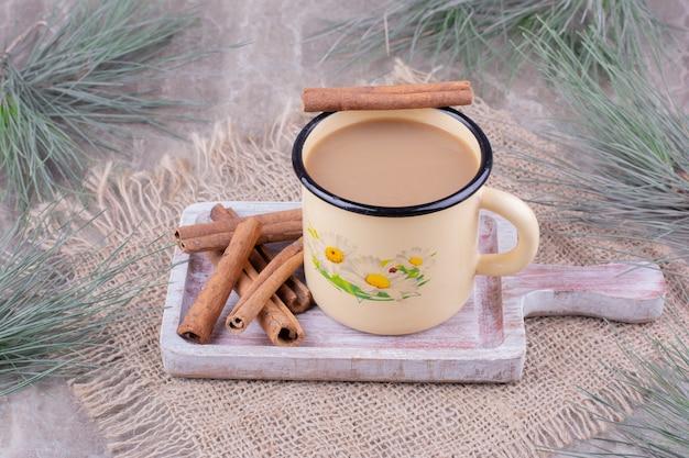 Een kopje koffie met kaneelstokjes op rustieke houten bord. Gratis Foto
