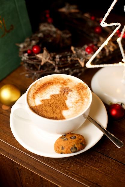 Een kopje koffie met latte kunst van de kerstboom Gratis Foto