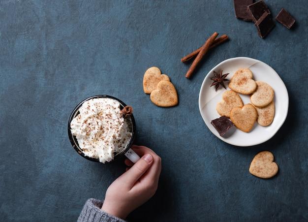 Een kopje koffie met room en chocoladeschilfers in de hand op een donkerblauwe tafel met zelfgemaakte koekjes, chocolade en kaneel. bovenaanzicht en kopieer ruimte Premium Foto