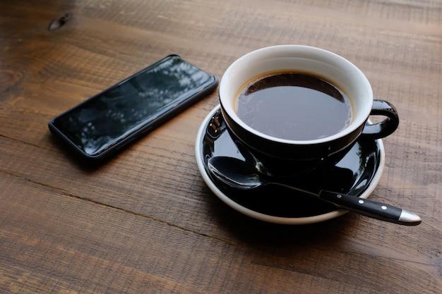Een kopje koffie op een houten tafel in het café. dichtbij de telefoon. ondernemingen. Premium Foto