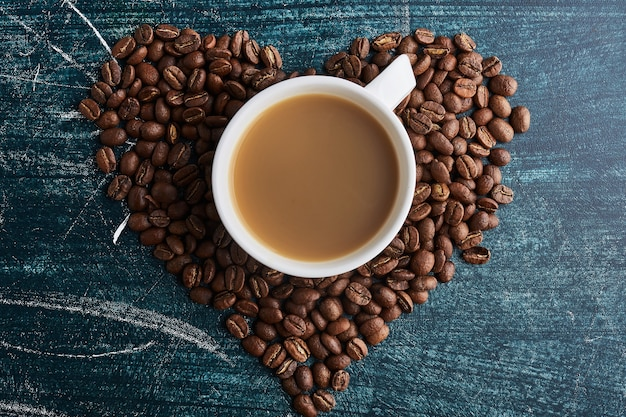 Een kopje koffie op granen in hartvorm. Gratis Foto