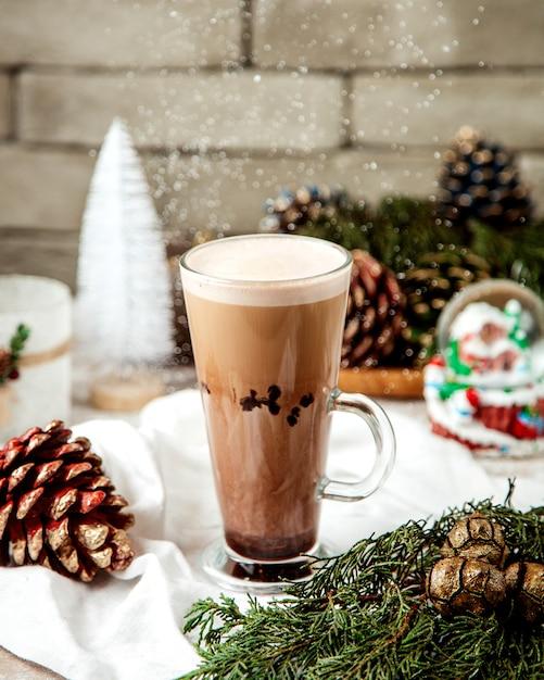 Een kopje latte naast kerstversiering Gratis Foto
