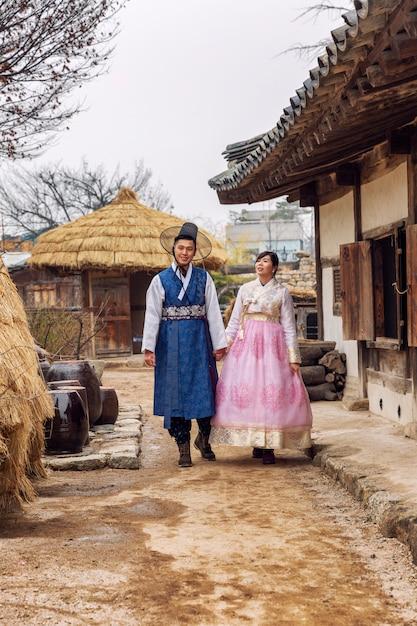 Een koreaans echtpaar in hanboks die door een prachtig park lopen Premium Foto