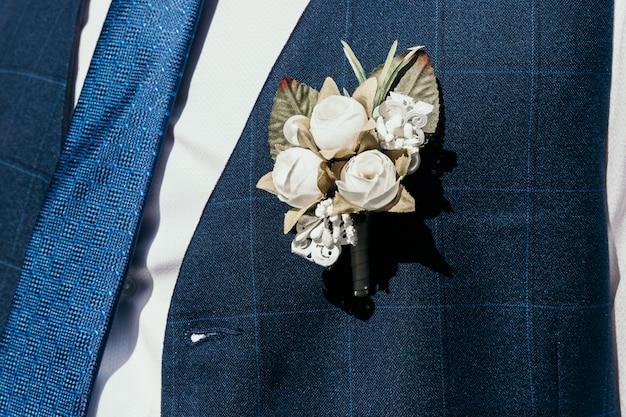 Een kunstmatig knoopsgat doorboord aan het vest van de bruidegom. Premium Foto