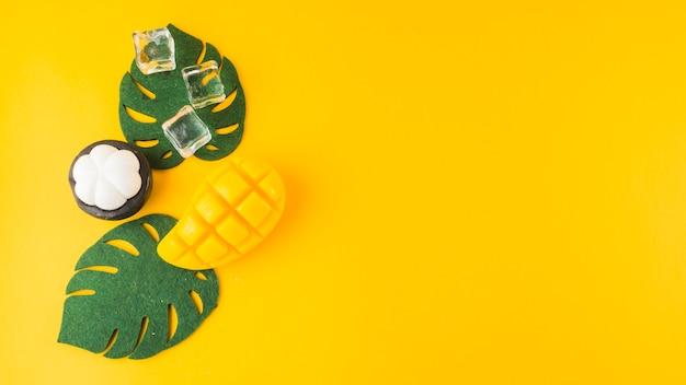 Een kunstmatige monstera vertrekt; mangosteen; ijsblokjes en mongo slice tegen gele achtergrond Gratis Foto