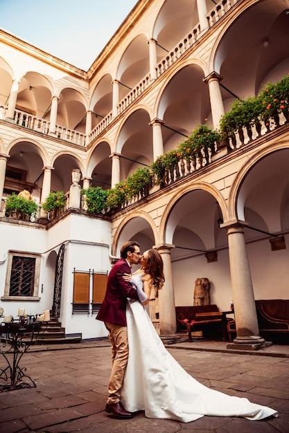 Een kus van een jong stel op de binnenplaats met een historische architectuur Premium Foto