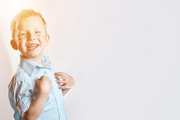 Een lachende gelukkige jongen in blauw shirt op licht Premium Foto