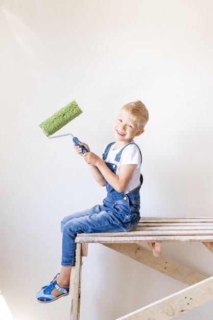 Een lachende kind bouwer zit op een bouwladder in een appartement met witte muren en houdt een kap voor het schilderen van muren, een plek voor tekst, een reparatie-concept Premium Foto