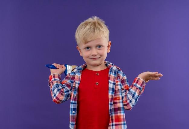 Een lachende schattige kleine jongen met blond haar, gekleed in een geruit overhemd met kwast op zoek op een paarse muur Gratis Foto