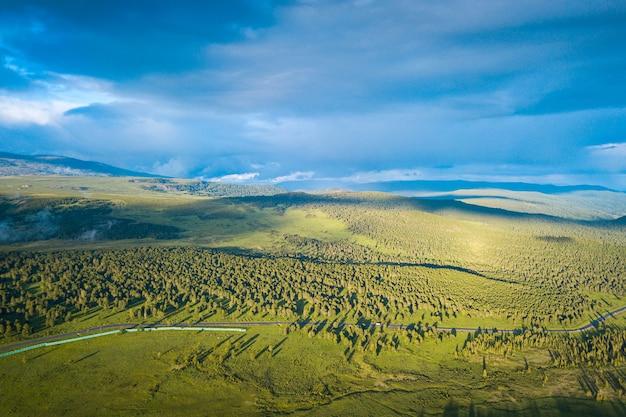 Een landschapsmening van mooi vers groen bos, weg chui-tract en altai-bergachtergrond. panoramisch uitzicht op het prachtige groene bos in de altai-bergen Premium Foto