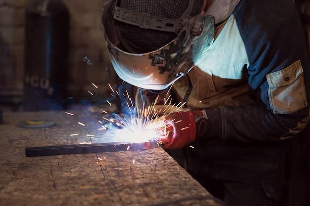 Een lasser die met het lassen van metaal werkt met een beschermend masker en vonken. Premium Foto