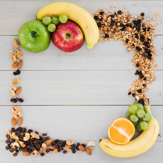 Een leeg frame gemaakt met gedroogde vruchten; haver en fruit op houten bureau Gratis Foto