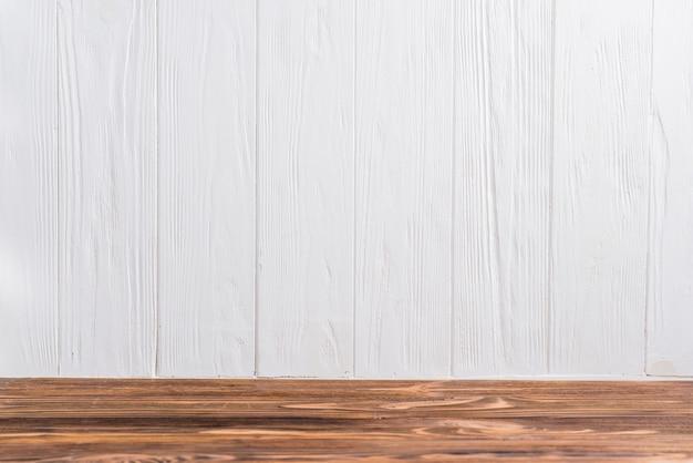 Een leeg houten bureau tegen witte geschilderde muur Gratis Foto