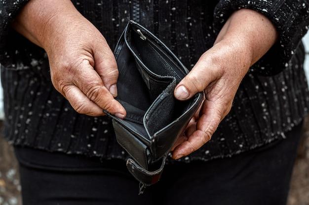 Een lege portemonnee in de handen van een gepensioneerde. Premium Foto