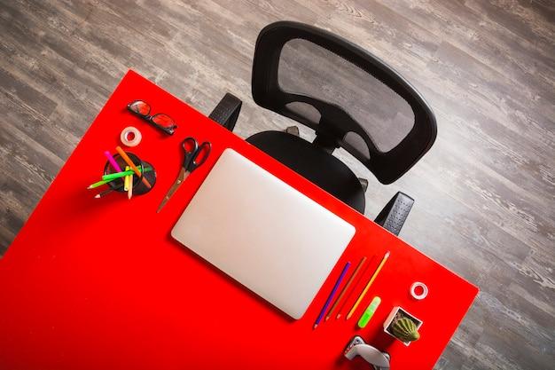 Een lege zwarte stoel op kantoorwerkplek met laptop en kantoorbehoeften op rode lijst Gratis Foto
