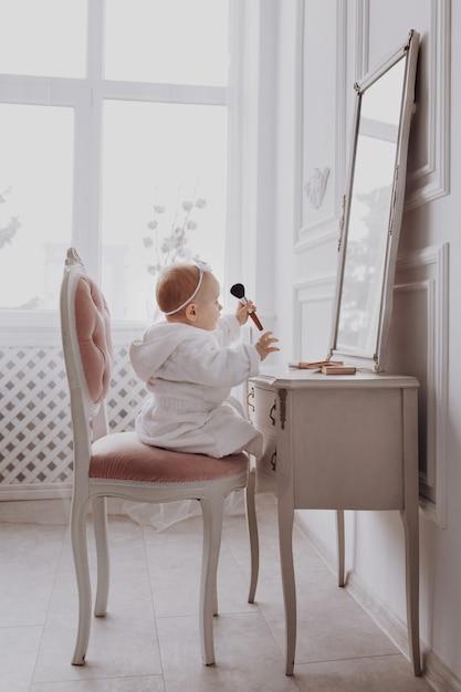 Een leuke kleine vrouw houdt een make-upborstel en heeft thuis pret. het babymeisje zit binnen op de stoel dichtbij de klassieke spiegel. kindermode. klein meisje fashionista. Premium Foto