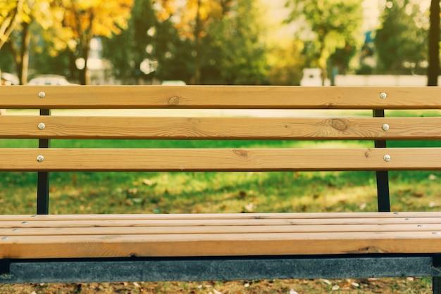 Een lichtbruine houten bank in park Premium Foto