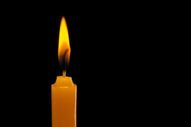 Eén lichtkaars brandt fel. studio opname geïsoleerd op zwart Premium Foto