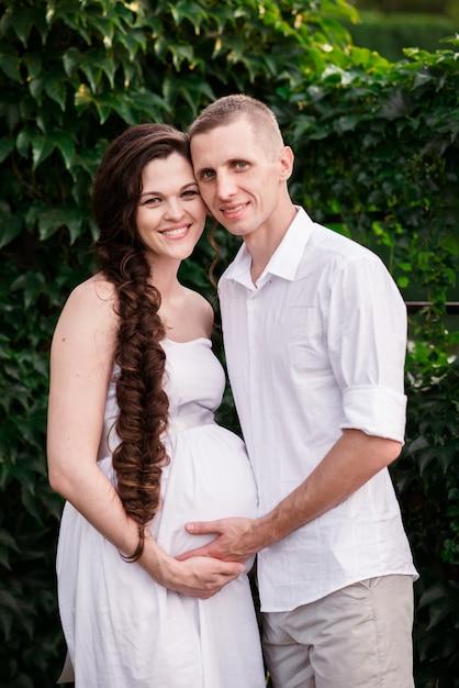 Een liefdevol zwanger paar knuffels in een zomer park en glimlacht Premium Foto