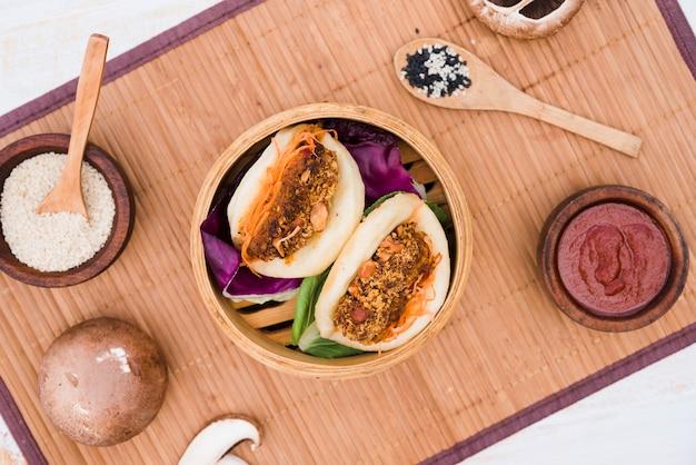 Een luchtmening van aziatische sandwich gestoomde gua bao-broodjes in stoomboot op placemat Gratis Foto