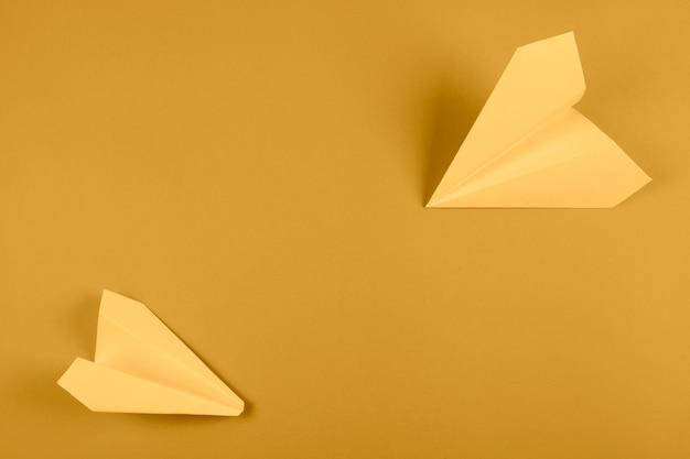 Een luchtmening van geel document vliegtuig op heldere gekleurde achtergrond Gratis Foto