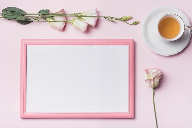 Een luchtmening van theekop met omlijsting en eustomabloemen tegen roze achtergrond Gratis Foto