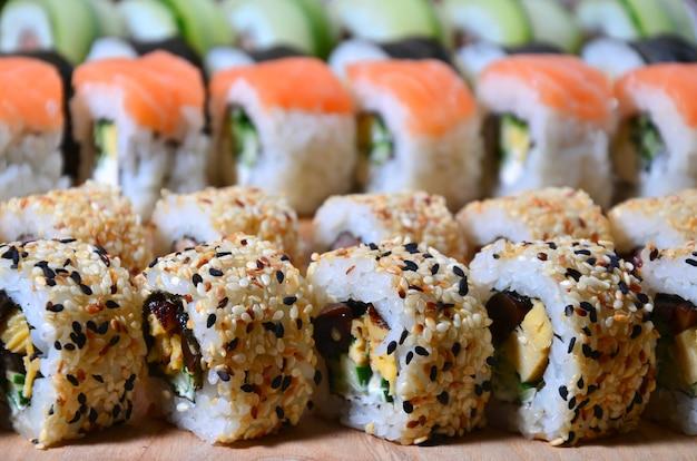 Een macroschot van een sushireeks vele broodjes wordt gevestigd op een houten scherpe raad op een lijst in de keuken van een sushistaaf. Premium Foto
